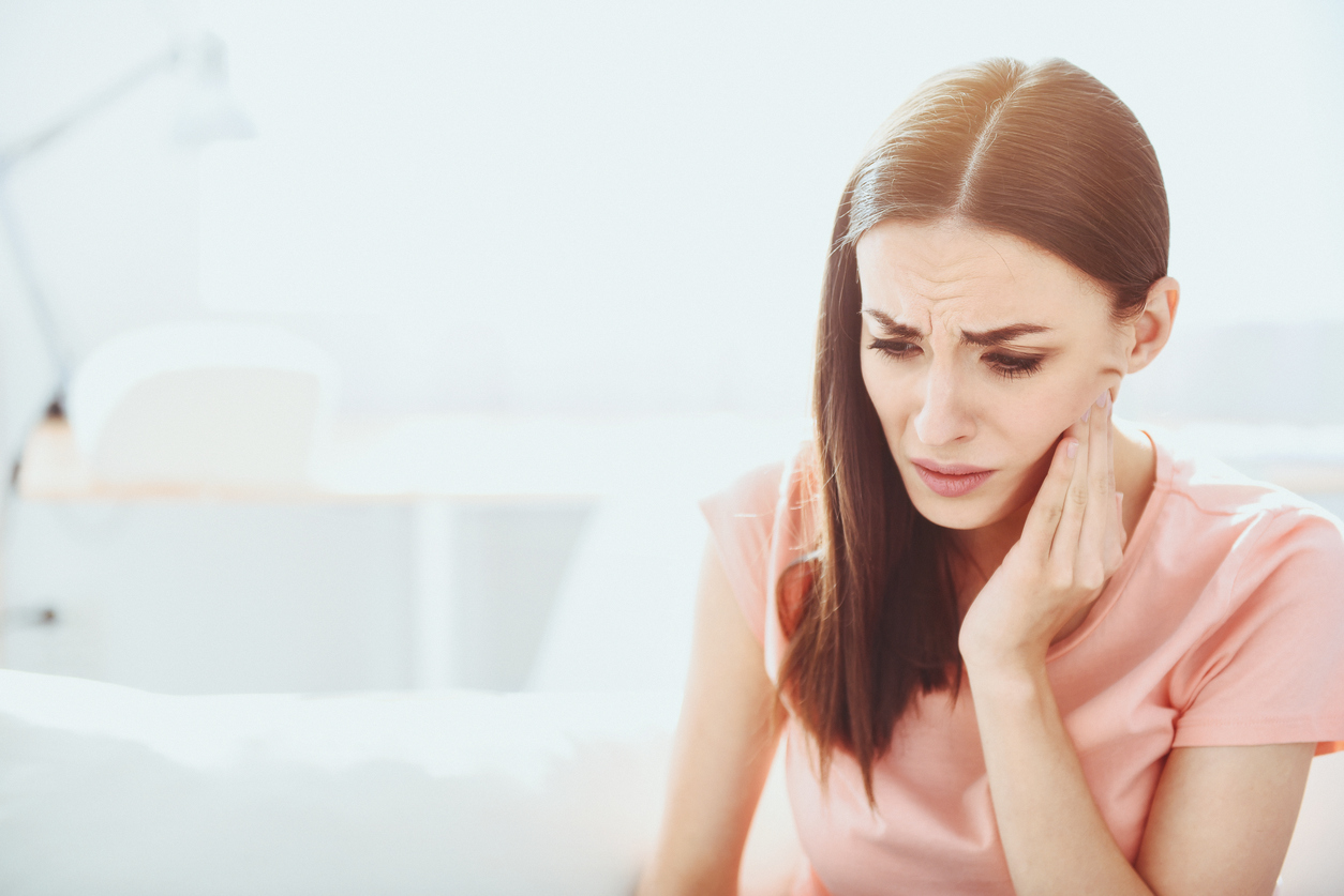 Close up of pretty disappointed woman which having toothache.